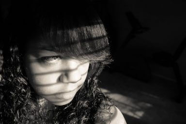 A somber looking girl with bangs stares out the window as a representation of the signs of depression