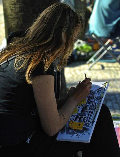 A girl draws outside as an example of healthy coping mechanisms