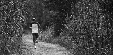 A man runs through a cornfield as he uses exercise to reinvent sobriety