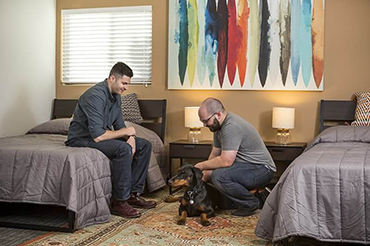 two men and their dog at the pet friendly Morningside Recovery rehab center